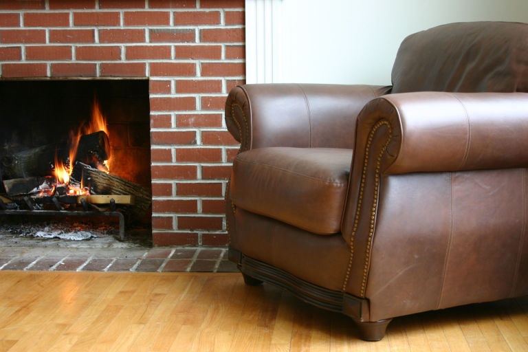 leather chair brick feature wall and fireplace