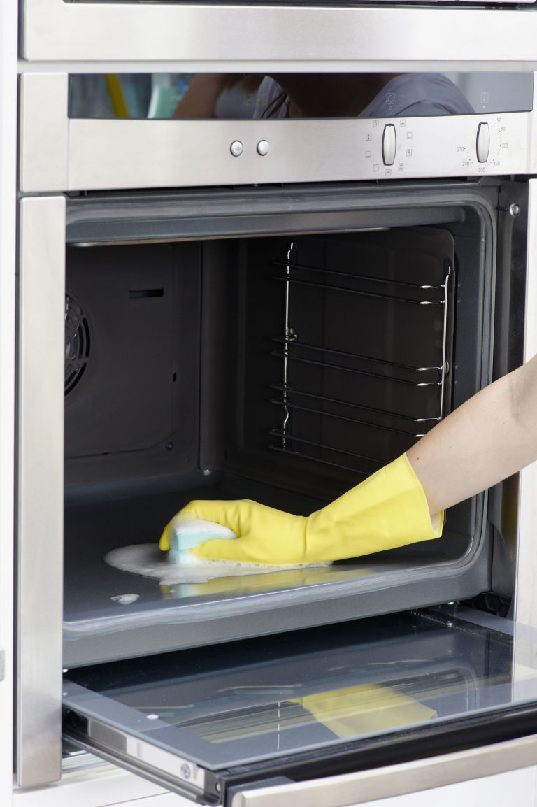 Oven cleaning step by step guide from professional cleaners on woman wearing yellow washing up glove to clean inside oven using sponge eventelaan Gallery