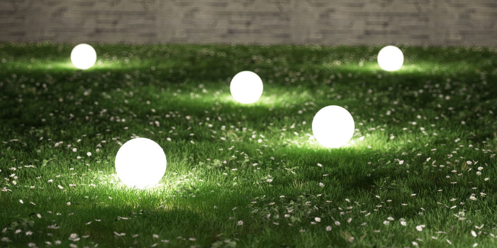 Illuminated Lamps On Grassy Field In Garden